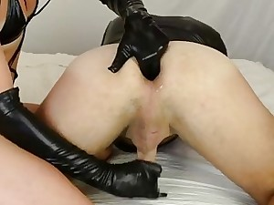 Blondie Mistress wears leather gloves for her slave's prostate exam